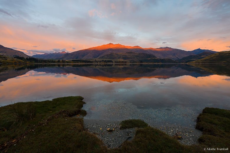 The rising sun paints the clouds pink and illuminates the top of Mount Hyde and is reflected in the still water of Glendhu Bay on Lake Wanaka on the South Island of New Zealand.