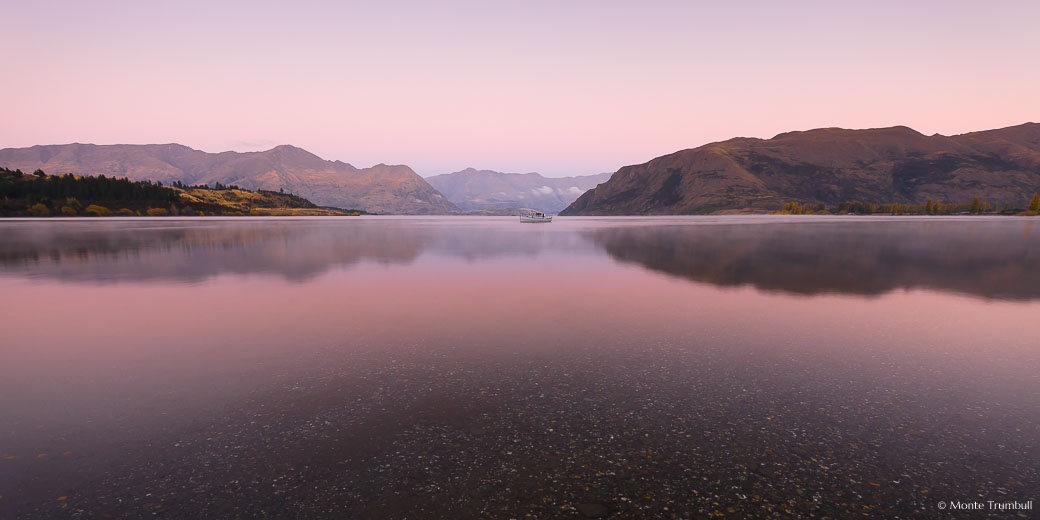 Predawn light bathes Lake Wanaka with soft pink light outside of Wanaka in New Zealand.