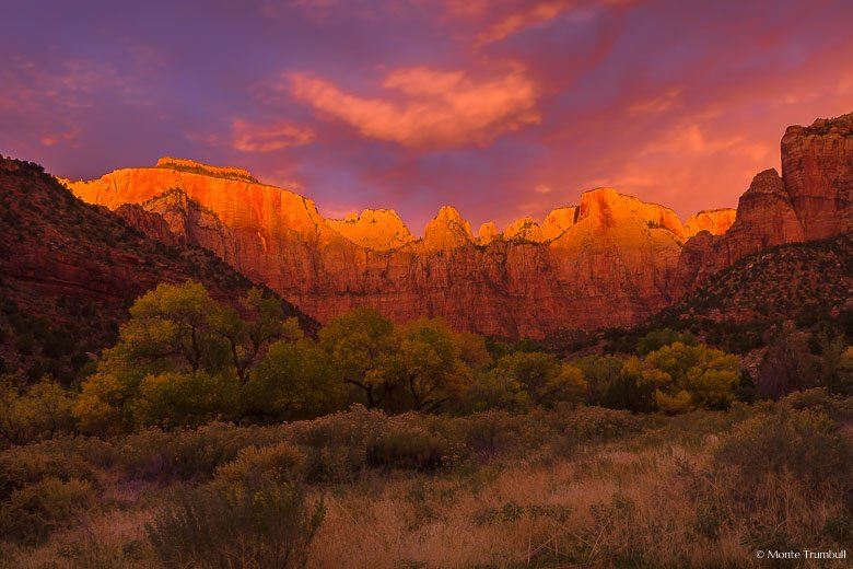 Stormy skies break and the scene is painted red at sunrise at the Towers of the Virgin in Zion National Park, Utah.