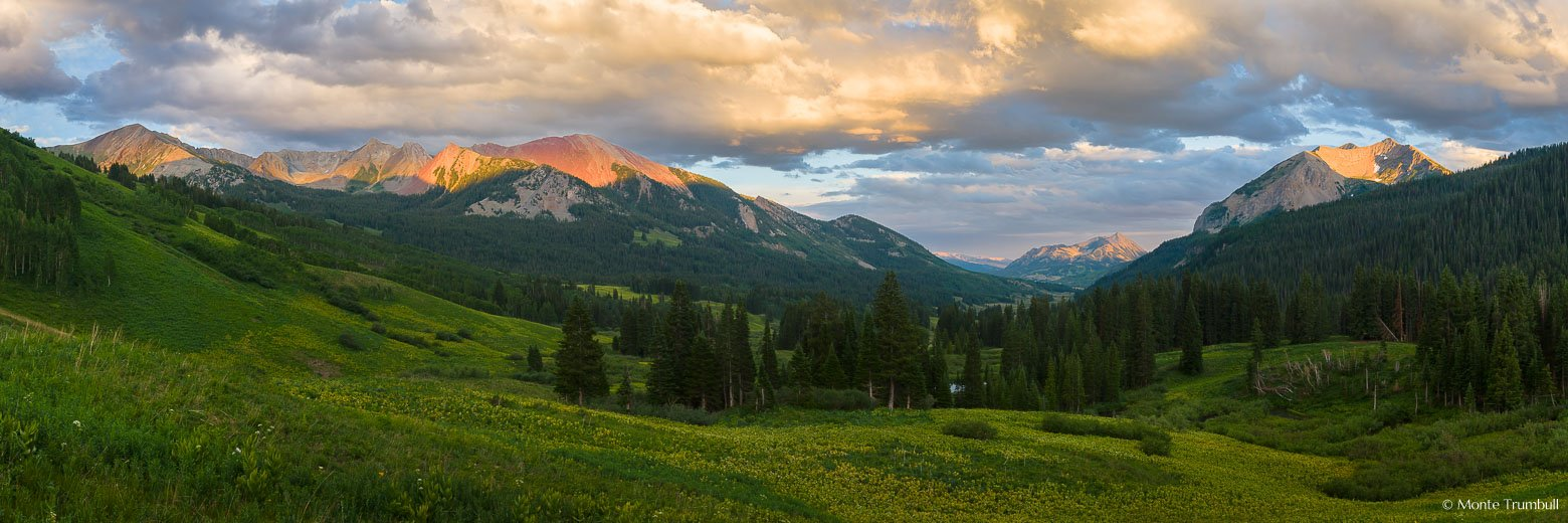 Dorothy Peak, Avery Peak, Crested Butte, and Gothic Mountain are lit by sunlight streaming through glowing clouds at sunset in this panoramic springtime scene looking down the East River Valley outside of Crested Butte, Colorado.