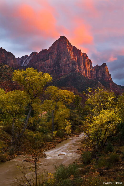 An ominous sky clears enough to let the setting sun through to illuminate The Watchman and the clouds above in Zion National Park, Utah.