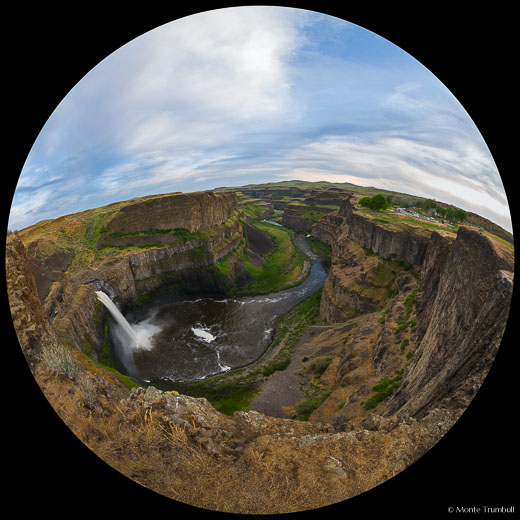A fish-eye view of the Palouse River gushing over Palouse Falls and flowing down a lush green valley into the distance on a beautiful spring day in Palouse Falls State Park in southeastern Washington.