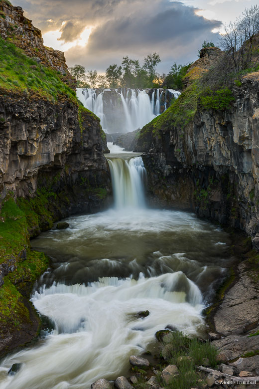 The White River thunders over White River Falls into a canyon lined by basalt walls covered in vibrant green moss before dropping over the smaller Celestial Falls on its journey downstream at Falls River State Park, Oregon.
