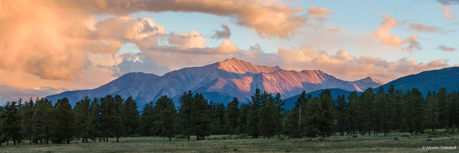 The last light of the day streams down a mountain valley and brushes the top of towering Mount Princeton outside of Buena Vista, Colorado.