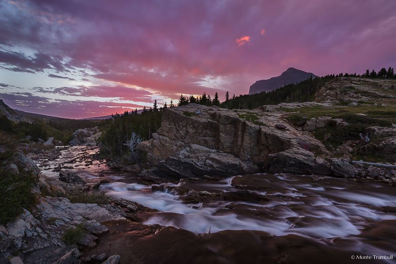 Swiftcurrent Creek rushes down Swiftcurrent Falls and flows down a valley towards the rising sun and a sky full of pink clouds in Glacier National Park, Montana.