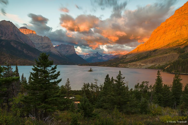 The rising sun streams across the tops of the mountains surrounding Saint Mary Lake painting the clouds and the mountainsides orange on a windy morning in Glacier National Park, Montana.