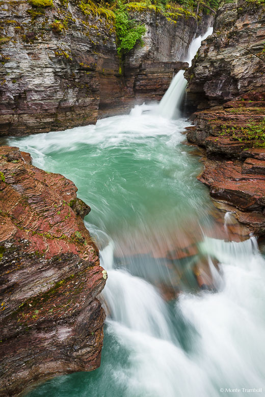 The Saint Mary River slices through a narrow rocky crevice and surges down Saint Mary Falls before taking a quick turn and rushing downstream towards Saint Mary Lake in Glacier National Park, Montana.