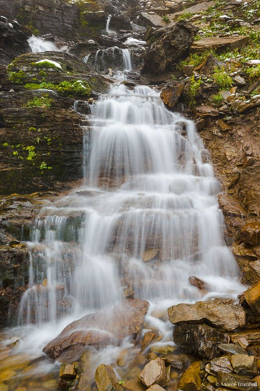 The headwaters of Logan Creek fan out and flow over Oberlin Falls high up in the mountains of Glacier National Park.
