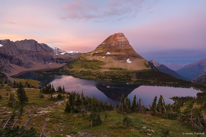 Pink skies surround Bearhat Mountain as it basks in the first light of dawn and is reflected in the waters of Hidden Lake high up in the mountains of Glacier National Park in Montana.