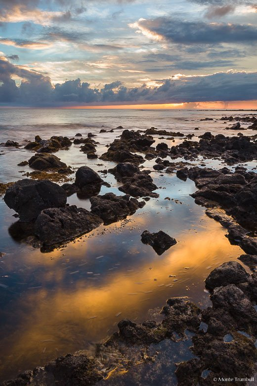 The setting sun peeks out from behind a cloud bank and reflects in tide pools along the rocky shore at Poipu Beach Park in Kauai, Hawaii.
