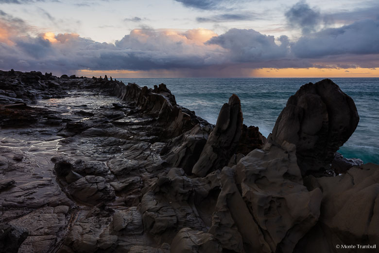 Stormy clouds and a rain squall over the ocean are illuminated by early morning light beyond the rocky Dragon's Teeth formation on the northwest coast of Maui, Hawaii.