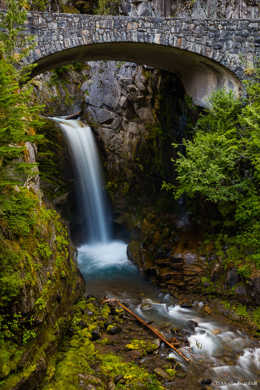 Van Trump Creek drops gracefully over the lower section of Christine Falls and flows underneath a rustic stone bridge in Mount Rainier National Park, Washington.