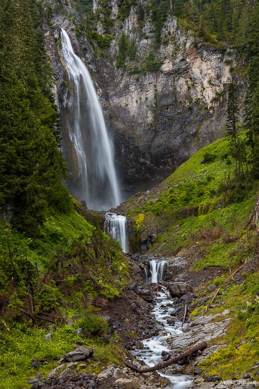 Van Trump Creek drops abruptly from the top of a massive cliff wall forming Comet Falls which plunges in a series of three steps into a lush green valley over 450 feet below in Mount Rainier National Park, Washington.