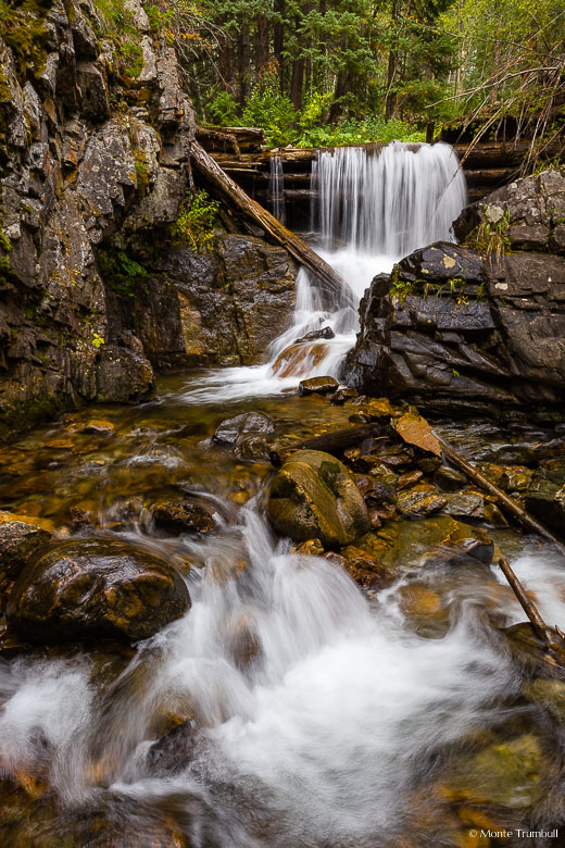 French Creek Falls spills over a log jam and winds its way through a rocky section on its race down a steep mountainside in the White River National Forest outside of Minturn, Colorado.