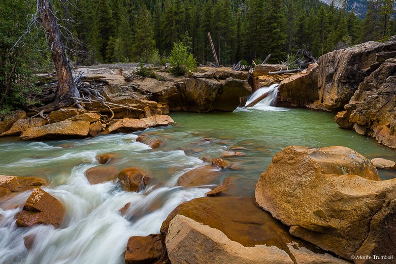 Lake Creek drops through a log jam and over Snyder Falls before winding through red rock walls on its way downstream in the San Isabel National Forest in Central Colorado.