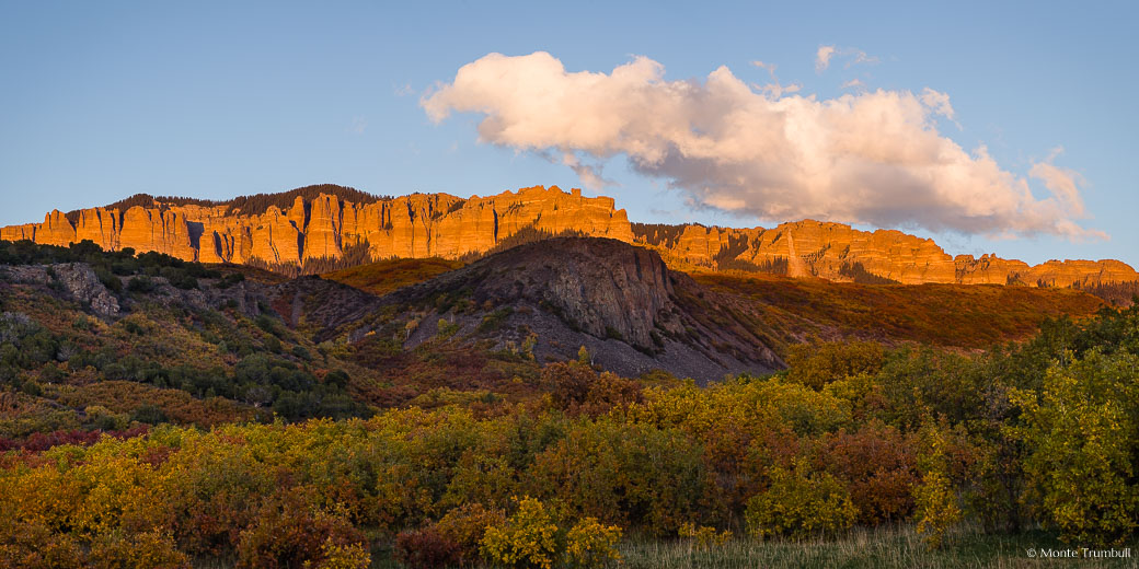 The fleeting autumn rays of the setting sun light up the face of a section of the Cimarron Ridge behind a valley filled with multi-colored brush outside Ridgway, Colorado.