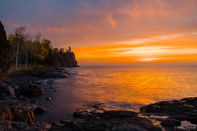 The sun begins to break through a bank of clouds and casts a golden glow on Split Rock Lighthouse perched along the rocky coast of Lake Superior in northern Minnesota.