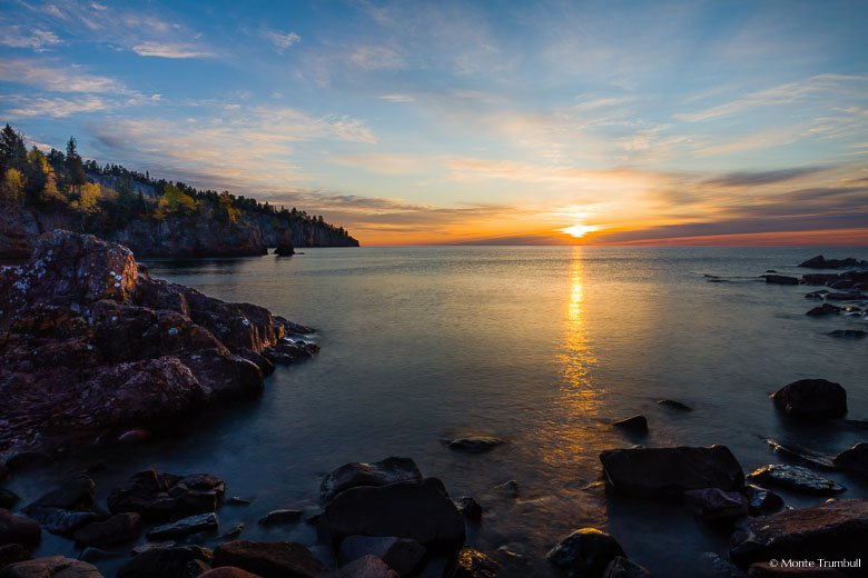 The sun peeks through the clouds as it rises above Lake Superior, shining light on Shovel Point and a rocky shoreline in Tettegouche State Park along the North Shore of Minnesota.