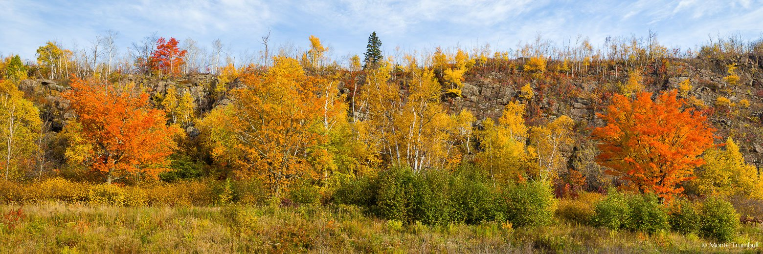 A rocky hillside is covered with a variety of trees and shrubs at the peak of fall color outside of Silver Bay on the North Shore of Minnesota.