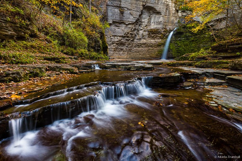 McClure Creek plunges over Eagle Cliff Falls and then over a series of rocky shelves in a narrow, rocky canyon sprinkled with autumn leaves in Havana Glen Park outside of Montour Falls, New York.