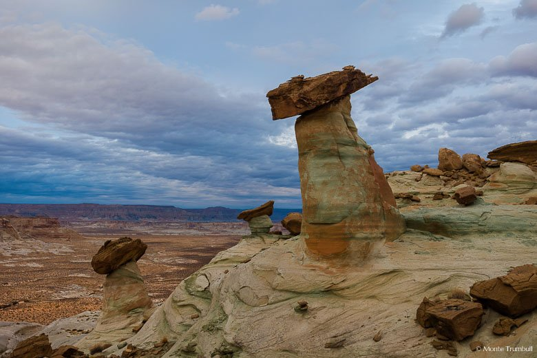 A group of stone hoodoos perched along Stud Horse Point overlook a desert valley below with foreboding evening skies overhead outside of Page, Arizona.