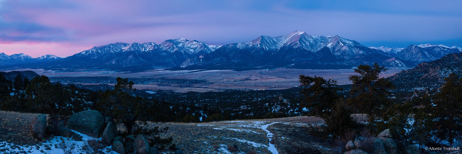 The Arkansas River valley and the Sawatch Mountains in the distance are bathed in soft pink light at dawn on a winter morning outside of Buena Vista, Colorado.
