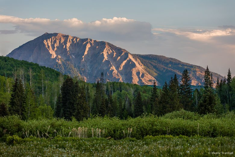 Marcellina Mountain basks in early morning sunlight beyond a lush green meadow in the Gunnison National Forest outside of Crested Butte, Colorado.