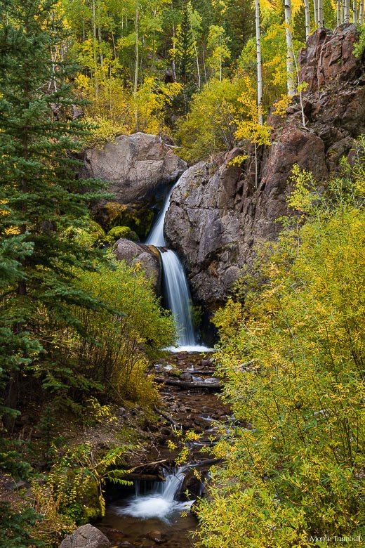 Nellie Creek Falls gracefully steps its way through a forest filled with the golds and greens of early autumn in the Gunnison National Forest outside of Lake City, Colorado.
