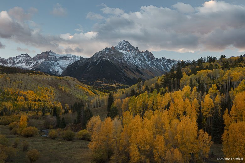 A few rays from the setting sun shine through glowing clouds and illuminate the side of Mount Sneffels above a valley filled with golden aspen trees in the Uncompahgre National Forest outside of Ridgway, Colorado.