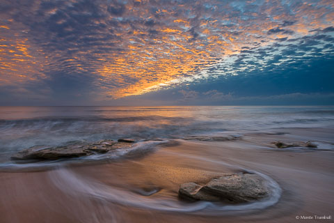 The rising sun illuminates the breaking cloud cover over a rocky beach in Washington Oaks Gardens State Park, Florida.