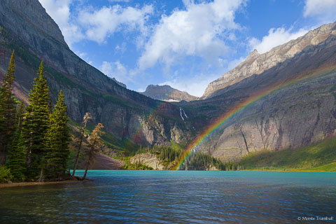 A rainbow appears as the sun breaks through the clouds during a morning shower at Grinnell Lake in Glacier National Park in Montana.