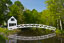 The brilliant white Somesville Bridge and surrounding spring green trees are relflected in calm water in Somesville, Maine.