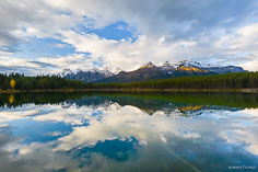 The snow capped Bow Range mountains reflect in Herbert Lake at Banff National Park, Alberta, Canada.