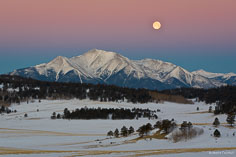 The full moon sets through the Earth's shadow over Mt. Princeton on a cold winter morning outside Buena Vista, Colorado.