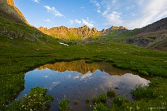 The mountains surrounding Clear Lake reflect in a tarn at sunrise outside of Silverton, Colorado.