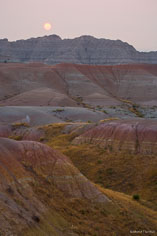 The sun shines through the haze above a landscape of colored rocks at Badlands National Park in South Dakota.