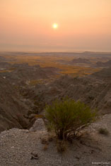 The sun rises through the haze over Badlands National Park in South Dakota.