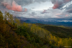 Dramatic clouds lit by sunset light hang over the Elk Mountains and a valley filled with fall color outside of Marble, Colorado.