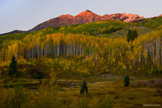 The last light of day turns Mt. Owen red while surrounded with golden aspens outside of Crested Butte, Colorado.