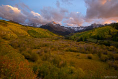 The last bit of sunlight illuminates the clouds and the peaks of the Sneffels Range beyond a valley filled with gold and green aspens outside of Ridgway, Colorado.