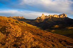 Sunset light on the gold and orange hillsides with Courthouse Mountain and Chimney Rock in the distance outside of Ridgway, Colorado.
