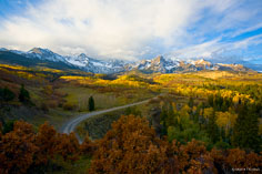 The rising sun illuminates the Sneffels Range behind a valley filled with golden aspen and rusty scrub oak outside of Ridgway, Colorado.