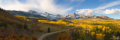 Panoramic image of the rising sun illuminates the Sneffels Range behind a valley filled with golden aspen and rusty scrub oak outside of Ridgway, Colorado.
