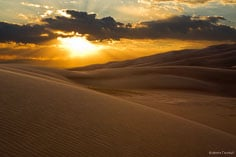 The setting sun spreads soft light over the dunes at Great Sand Dunes National Park outside of Alamosa, Colorado.