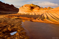 An icy pool stands before the sandstone swirls of The Second Wave in northern Arizona.