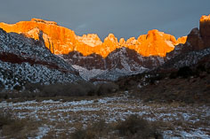 The Towers of the Virgin turn orange from the rays of the rising sun in Zion National Park in Utah.