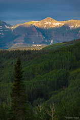 The sun lights up Storm Ridge beyond a valley of green aspens outside of Crested Butte, Colorado.
