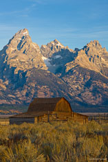 Sunrise lights up the Tetons behind a Morman Row barn outside of Jackson, Wyoming.