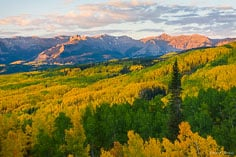 Beyond a valley filled with golden aspens, the rising sun lights up the Castles outside of Crested Butte, Colorado.