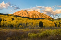Sunrise lights up East Beckwith Mountain as it towers above golden aspens outside of Crested Butte, Colorado.